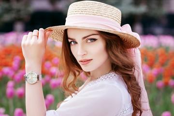 Beautiful girl wearing straw hat, wrist watch, blouse posing near tulips