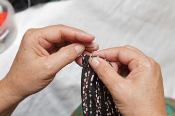 femme senior cousant une pochette en tissu