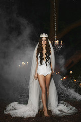 Beautiful young brunette model woman with a gentle makeup in white lingerie with a crown and veil on her head stands in a smoky forest and posing outdoors, bridal preparation of a young bride