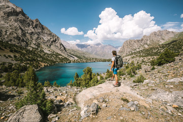 hiker standing above beautiful mountain lake in tajikistan