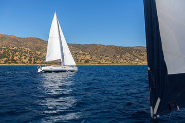 Ship yachts with white sails in the Sea. Luxury sailing boats.