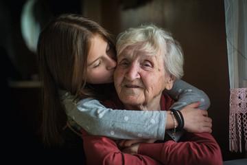A little girl hugs her grandmother.