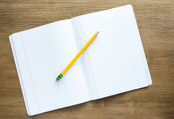 a yellow pencil on top of an open notebook with empty pages for a customized message on a wooden desk