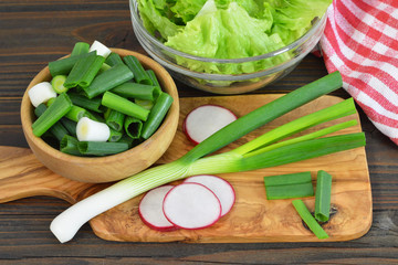 Green onions, radish and lettuce on wooden kitchen board