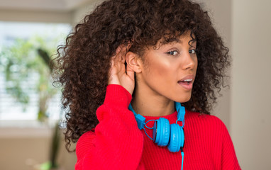 African american woman wearing headphones smiling with hand over ear listening an hearing to rumor or gossip. Deafness concept.
