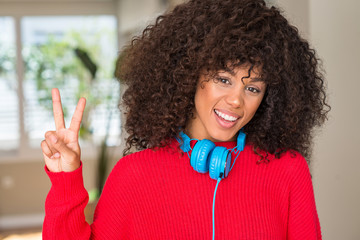 African american woman wearing headphones showing and pointing up with fingers number two while smiling confident and happy.