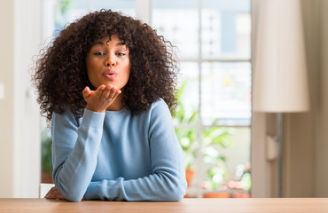 African american woman at home looking at the camera blowing a kiss with hand on air being lovely and sexy. Love expression.