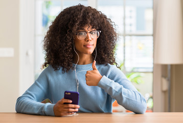 Beautiful african american woman using smartphone happy with big smile doing ok sign, thumb up with fingers, excellent sign