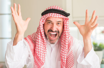Middle age arabian man at home very happy and excited, winner expression celebrating victory screaming with big smile and raised hands