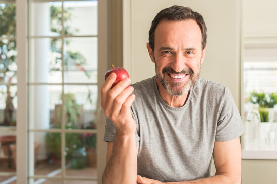 Middle age man eating healthy red apple with a happy face standing and smiling with a confident smile showing teeth