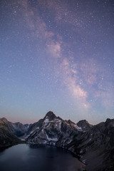 Pink sunset milky way over mountains