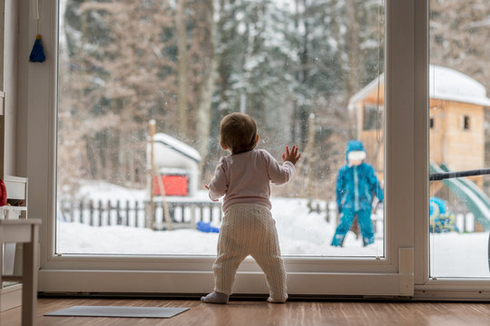 Little baby standing watching a sibling outdoors
