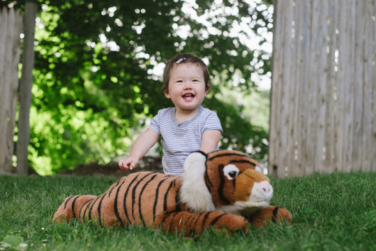 Happy baby with tiger stuffed animal outside