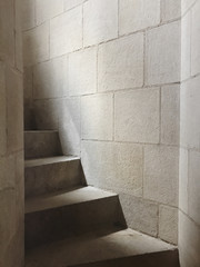 Detail of stairs leading up narrow corridor, sunlight filtering through small window
