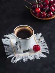 A cup of coffee and sweet cherries on a black table.