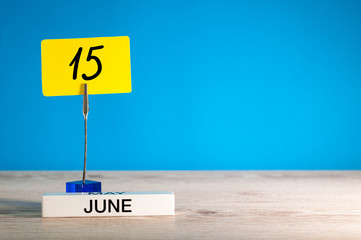 June 15th. Day 15 of june month, calendar on table with blue background. Summer time, empty space for text or template