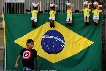 A Brazilian flag and dolls for sale are seen as a boy walks ahead of the 2018 World Cup, in Rio de Janeiro
