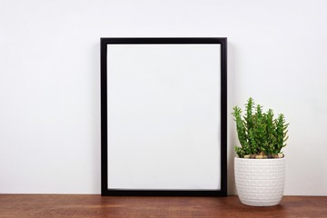 Mock up black frame with cactus plant on a shelf or desk. Wood shelf and white wall. Portrait frame orientation.