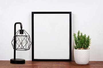 Mock up black frame, cactus plant and industrial style lamp on a shelf or desk. Wood shelf and white wall. Portrait frame orientation.
