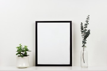 Mock up black frame with plant and branches on a shelf or desk. White shelf and wall. Portrait frame orientation.