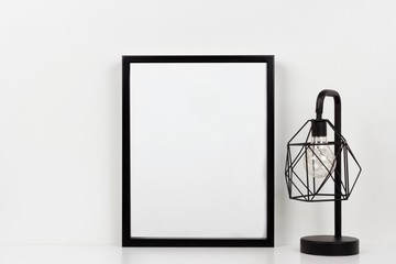 Mock up black frame and industrial style lamp on a shelf or desk. White shelf and wall. Portrait frame orientation.