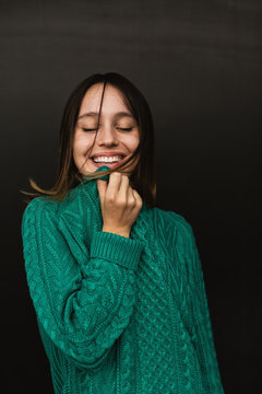 Portrait of a happy girl wearing green knitted sweater.