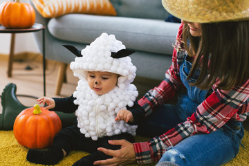 Young mother and her baby dressed up as farmer and little sheep for halloween.