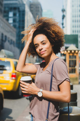 Woman standing in city with coffee