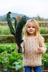 Blonde little girl holding a fresh vegetable in orchard.