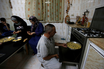 Abu Saleim and his family, who fled Syria seven years ago, make traditional sweets for the upcoming Eid celebrations at their home in Amman