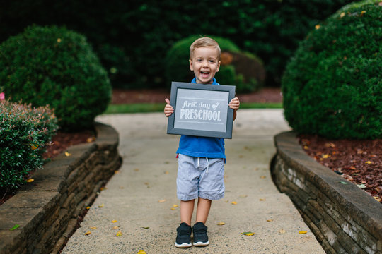 Cute young boy holding up a first day of preschool sign
