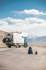young boy and his red parrot friend sitting on a road on the pamir highway beside a camping truck
