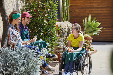Gardeners Sitting With Disabled Colleague At Greenhouse