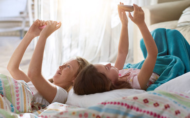 sisters in their bedroom using technology
