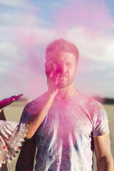 Woman throwing pink powder in young man?s face