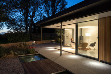 External picture of large glass doors of a garden room at night.