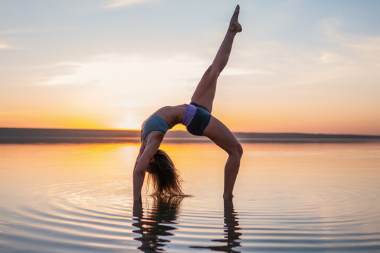 woman on the beach at sunset doing yoga asana. Morning natural stretch warm-up training