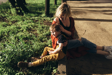 Mother and little son sitting on the roadside