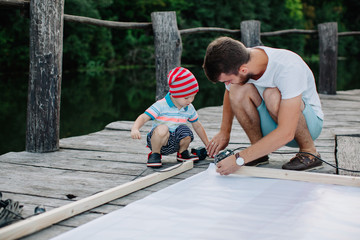 Little boy helping his father work with electric screwdriver outdoors
