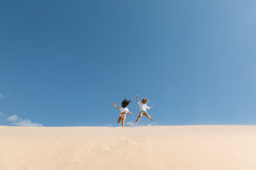 Teen girls jumping over beach dunes