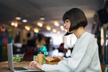 Woman working with laptop while having a lunch in a co-working office.