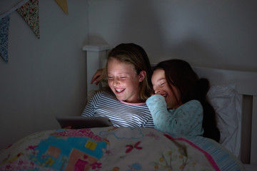 Young girls giggling together watching movies at bedtime