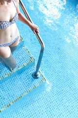 Woman entering in a pool