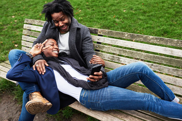 Funny couple making selfie on bench in park.