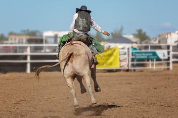 Cowboy Riding A Bucking Bull At A Rodeo