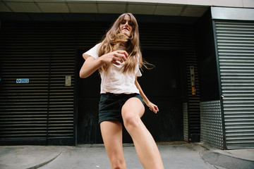An attractive young woman wearing shorts and T-shirt kicking her leg towards the camera