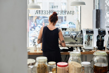 Back view of tattooed bartender working in cafe preparing fresh and delicious coffee for client.