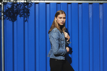 Blond girl posing against blue wall in wind
