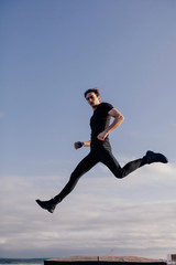 Young brunet wearing black jumping by the sky