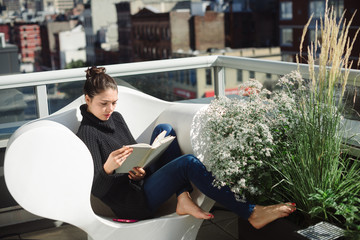 Young woman reading book on funky chair on balcony